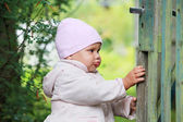 Baby girl in pink hat plays with old green wooden wicket — Stock Photo