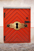 Old red wooden door with lock and large keyhole, old fashioned safety concept — 图库照片