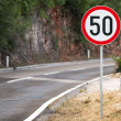 Stock Photo: Round speed limit road sign on mountain road