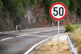 Round speed limit road sign on mountain road — Stock Photo