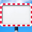 Empty white road sign with red striped frame above blue sky — Stock Photo