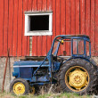 Small blue tractor stands on grass nearby red barn wall in Norway — Stock Photo