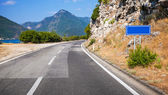 Mountain asphalt road and empty blue road sign in Montenegro — Stock Photo