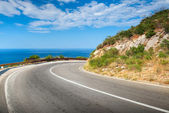 Turn of mountain asphalt road with blue sky and sea on a background — Stock Photo