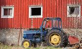 Маленький синий трактор стоит на траве рядом красный сарай стены в Норвегии — Стоковое фото