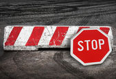 Red and white striped concrete road barrier and stop road sign lying on the pavement — Stock Photo