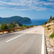 Mountain road with blue cloudy sky and sea on a background. Adriatic sea coast, Montenegro — Stock Photo