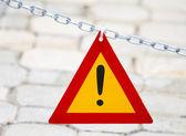 Parlak kırmızı ve sarı üçgen ünlem işareti metal zincir üzerinde asılı — Stok fotoğraf