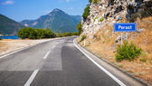 Mountain asphalt road and blue road sign with Perast town name in Montenegro — Stock Photo