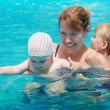 Mother and her daughters swim in bright blue sea water. Outdoor summer group portrait of young Caucasian real family — Stock Photo