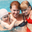 Mother and two her daughters smile in bright blue sea water. Outdoor summer group portrait of young Caucasian real family — Stock Photo