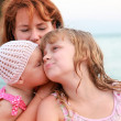 Young Caucasian family on the sea coast. Young mother with her kissing daughters — Stock Photo