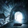 Glowing exit from dark abandoned tunnel. Monochrome blue photo — Stock Photo #31412667