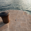 Stock Photo: Old rusted metal bollard stand on stone pier in Montenegro