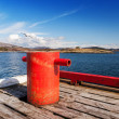 Stock Photo: Red mooring bollard on wooden pier in Norway
