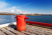 Red mooring bollard on wooden pier in Norway — Stock Photo