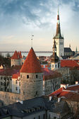Old town of Tallinn. Houses, fortress towers with red roofs and church St. Olaf — Stock Photo