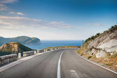Right turn of mountain highway with blue sky and sea on a background — Stock Photo