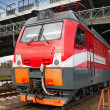 Stock Photo: Closeup photo of modern red locomotive on railway station