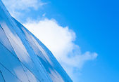 Modern abstract architecture background with steel wall panels and blue cloudy sky — Stock Photo