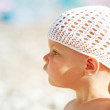 Outdoor summer profile portrait of curious Caucasian baby girl in white hat on the beach — Stock Photo #32310505