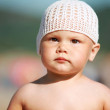Outdoor summer portrait of Caucasian baby girl in white hat on the beach — Stock Photo