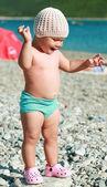 Caucasian baby balancing with laugh on big coastal stone — Stock Photo
