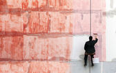 Painter works on the outer building wall with red priming paint — Stock Photo