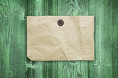 Empty yellow paper ad hanging on green vintage wooden wall — Stock Photo