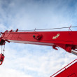 Red truck crane boom with hooks and scale weight above blue sky — Stock Photo
