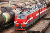 Modern red diesel electric locomotive rides on railway tracks with freight coaches — Stock Photo