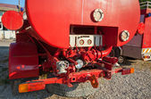 The rear of old red fire truck with water pump equipment — Stock Photo