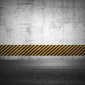 Abstract parking interior fragment with asphalt ground and striped yellow and black pattern on the concrete wall — Stock Photo