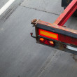 Back part with taillight of empty truck cargo trailer on the asphalt road — Stock Photo