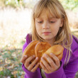 Little blond girl on a picnic in autumn park with small pies — Stock Photo