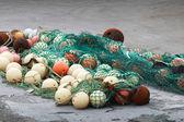 Yeşil balık ağı ile küresel şamandıralar kıyısında yatıyordu — Stok fotoğraf