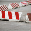 Red and white striped concrete road barriers lying on the asphalt pavement — Stock Photo