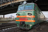 Green locomotive with red stripes on the cabin stands under the bridge on the railway station — Stock Photo