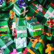 Photo background with huge pile of green shining gift boxes with colorful bows — Stock Photo