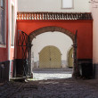 Old town of Tallinn, street fragment with red arch and wooden gate — Stock Photo