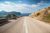 Dividing line and right turn sign on the coastal mountain highway in Montenegro — Stock Photo