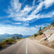 Mountain highway perspective with dramatic cloudy sky — Stock Photo #34043689