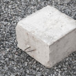 Stock Photo: Big concrete construction block with metal lug on gray gravel