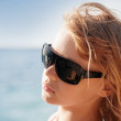 Stock Photo: Little blond girl portrait with sunglasses on the summer sea coa
