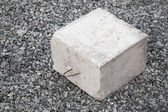 Big concrete construction block with metal lug on gray gravel — Stock Photo