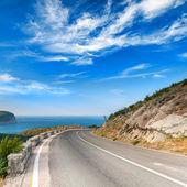 Wendung der berg autobahn mit dramatischen blauer himmel und meer — Stockfoto