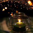 Green candle burns in candlestick made of glass with Christmas lights garland bokeh on background — Zdjęcie stockowe