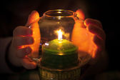 Child warm their hands at green candle burns in candlestick made of glass — Stok fotoğraf