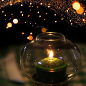 Green candle burns in candlestick made of glass with Christmas lights garland bokeh on background — Foto Stock