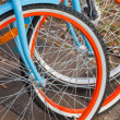 Colorful bicycles for rent stand in a row on a parking — Stock Photo #34459853